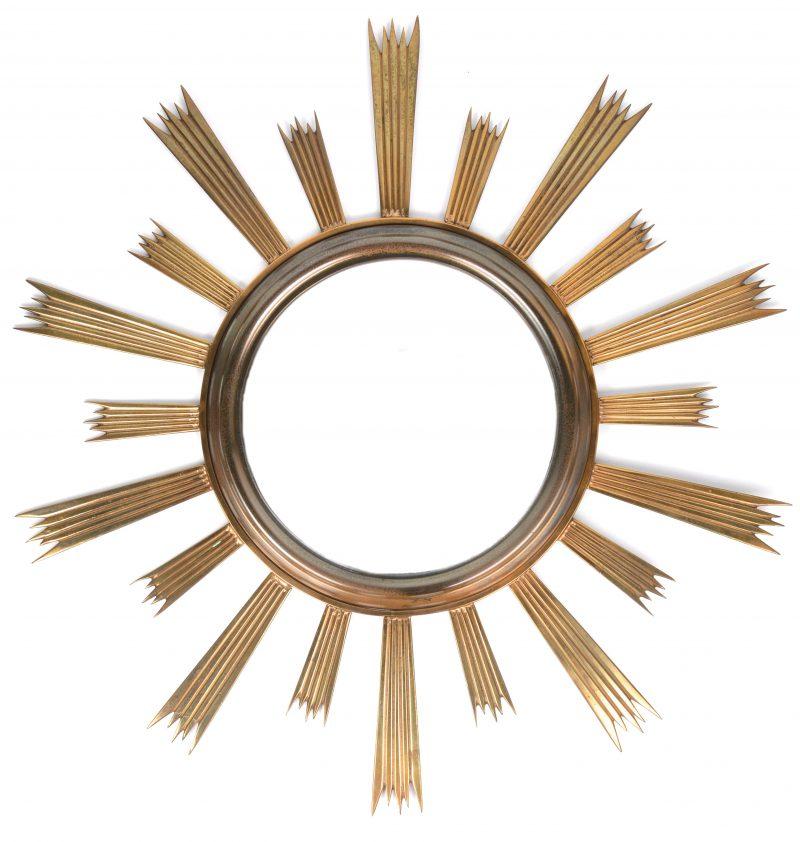 Een butlrspiegel met messingen lijst met zonnestralen.