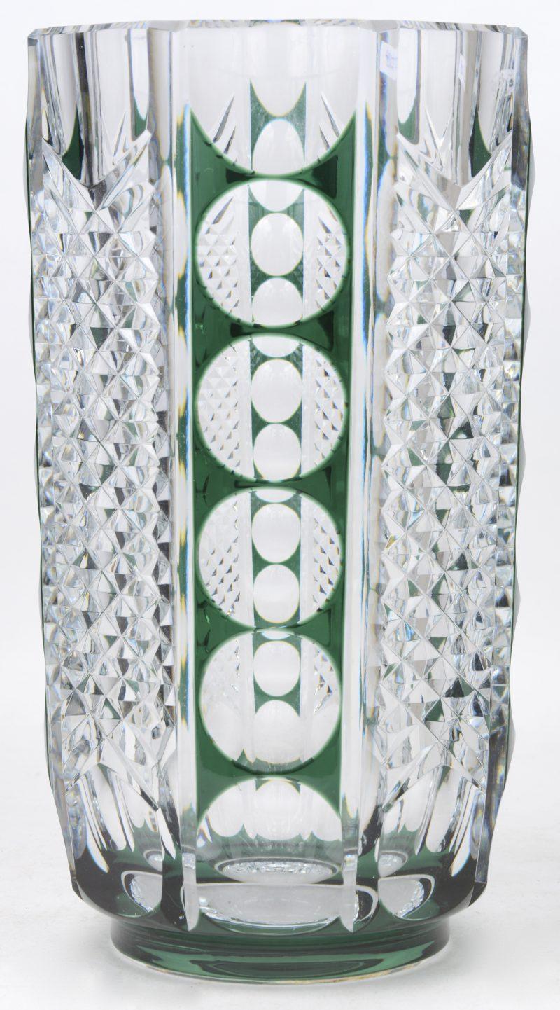 Een vaas van groen en kleurloos kristal met een in ruiten en bollen geslepen motief. Onderaan gemerkt.