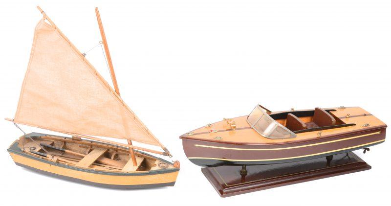 Twee scheepsmaquettes, waarbij een motorboot en een zeilboot.