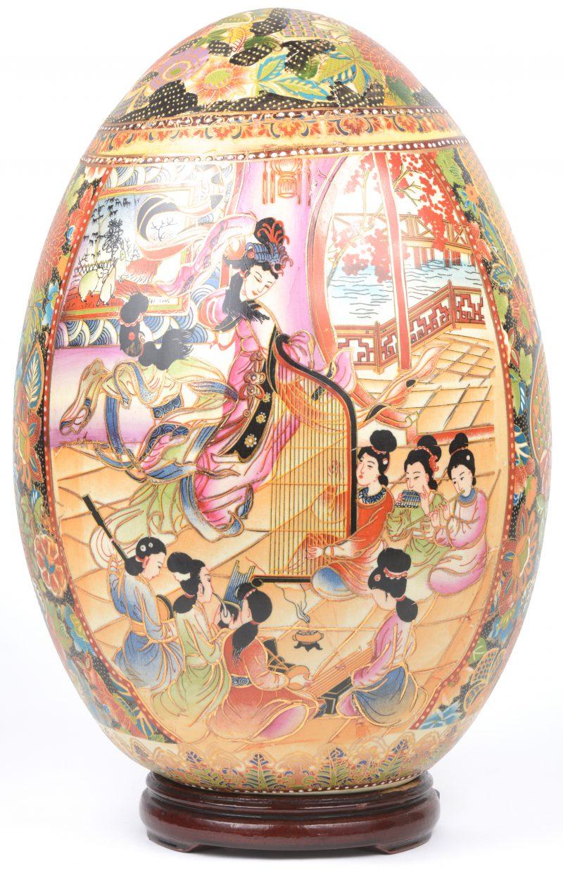 Een ei van Satsuma-aardewerk met een meerkleurig decor van bloemen en muziek spelende personages.
