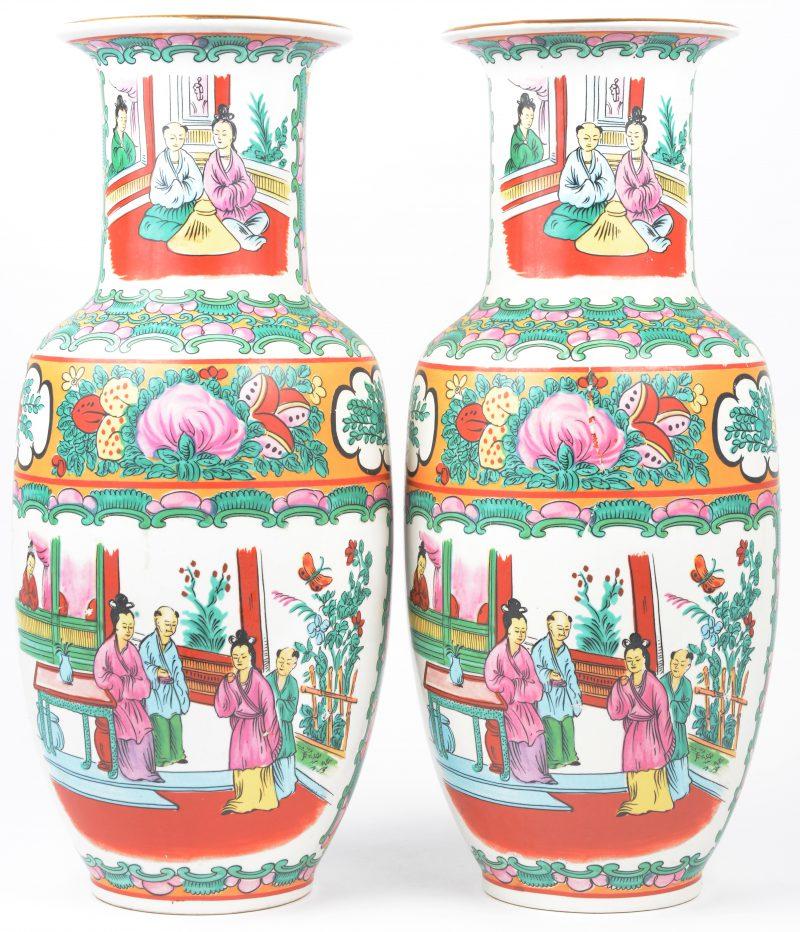 Een paar vazen van Chinees porselein met meerkleurige decors van personages. Onderaan gemerkt.