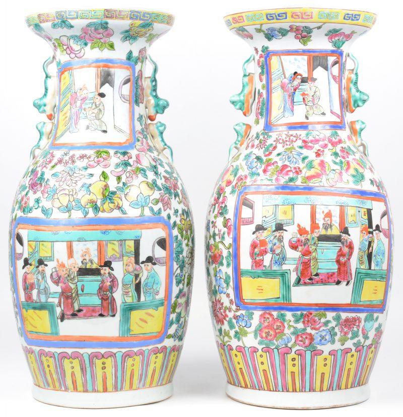 Een paar vazen van Chinees porselein met een meerkleurig decor van personages aan het hof in cartouches op een achtergrond van bloemen en perziken. Eén gemerkt onderaan.