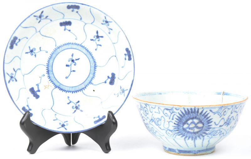 Een kom van blauw en wit Chinees porselein op onderschotel. Bakfout.