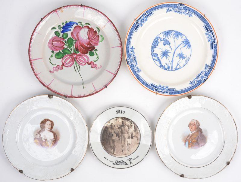 """Een lot borden van porselein en aardewerk: een paar met afbeelding van Lodewijk XVI en Marie-Antoinette (Saint-Amand), een met een blauw en wit decor """"Kenya"""" (Woodsware), één met een rozentuil (Staatsburg), een souvenirbordje van Rio de Janeiro met foto (Steatita Brasil, jaren zeventig)."""
