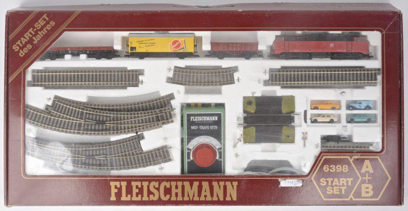 Een starttersset op schaal HO, met een diesellocomotief van de Duitse spoorwegen met drie goederenwagons, een groot deel rails met overweg en vier autootjes. In originele doos.