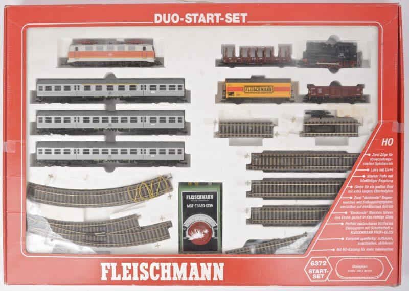 Een duo-startersset met een elektrische locomotief met drie passagierswagons  en een tenderlocomotief met drie goederenwagons. In originele doos.