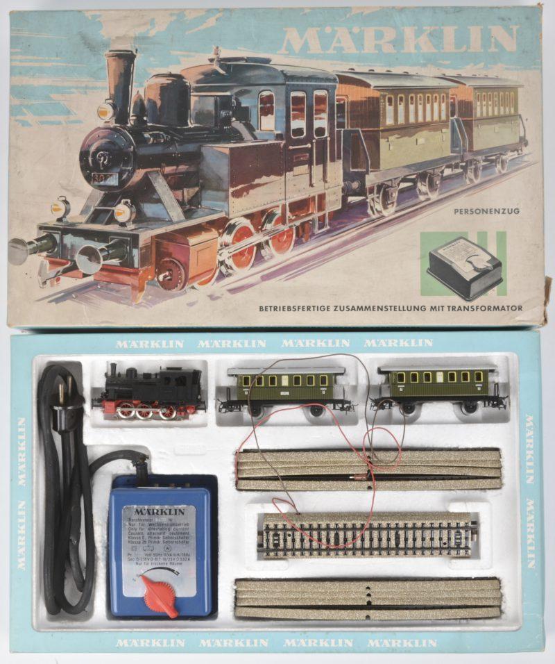 Een startersset met een tenderlocomotief met twee passagierswagons, een deel sporen en een transformator. Transformator in slechte staat. In originele doos.