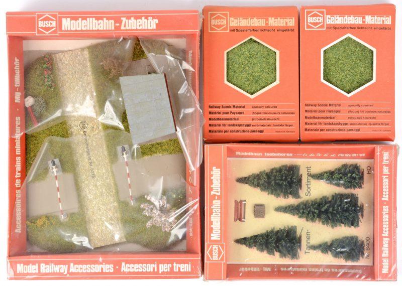 Een lot modelbouwaccesoires, bestaande uit een spoorwegovergang met seinhuis, een assortiment dennenbomen met bankje en twee doosjes strooisel voor bomen of gras. In originele verpakkingen.