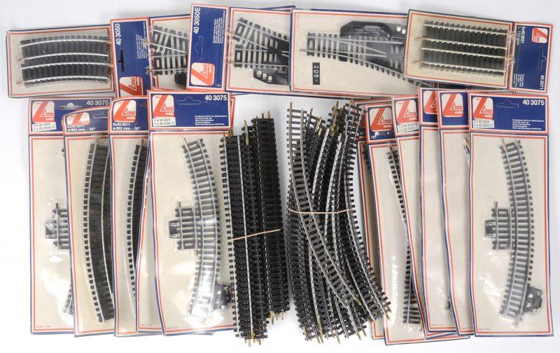Een gevarieerd lot rails, type HO, bestaande uit twee opzetrails, manuele en elektrische wissels, kruisingen, korte en lange rails, recht en gebogen en enkele rails met elektrische aankoppelingen. Grotendeels in ongeopende verpakkingen.