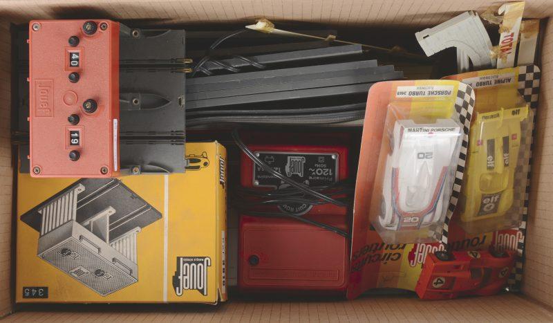 Een elektrische speelgoed racebaan met transformator, twee toerentellers en vier autootjes, waarbij twee in ongeopende verpakkingen. We voegen er een deel baanstukken van Polistil in originele dozen aan toe.
