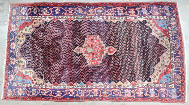 Een handgeknoopt Perzisch wollen tapijt met certificaat.