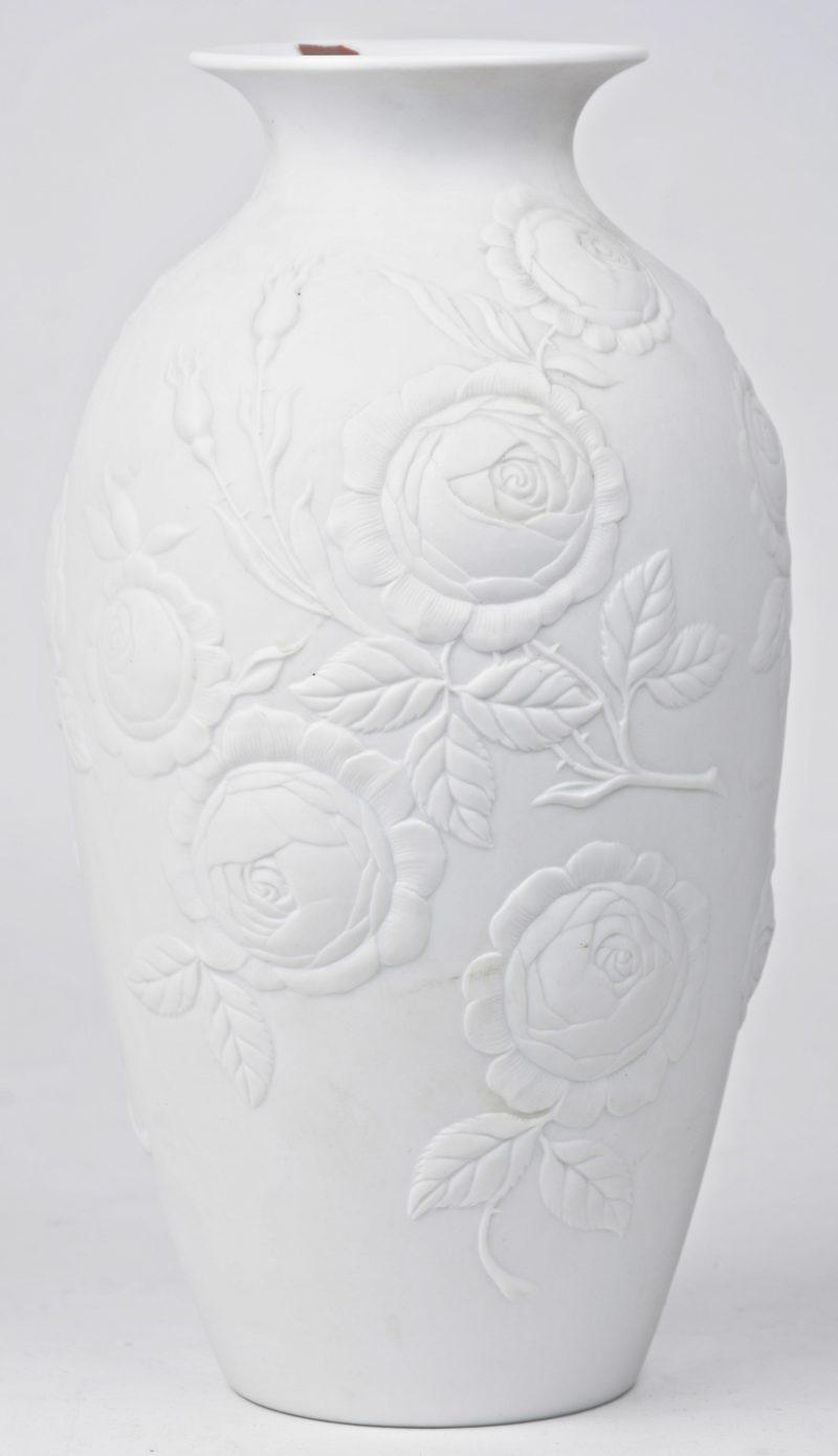Een balustervaasje van monochroom wit biscuit met een reliëfdecor van rozen. Gemerkt.