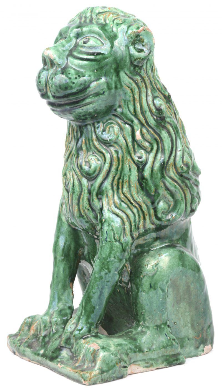 Een zittende leeuw van terracotta met groen glazuur.