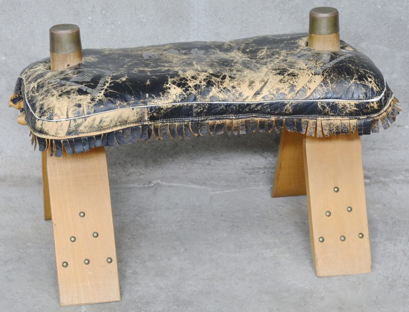 Een voetbankje van kamelenleer en hout.