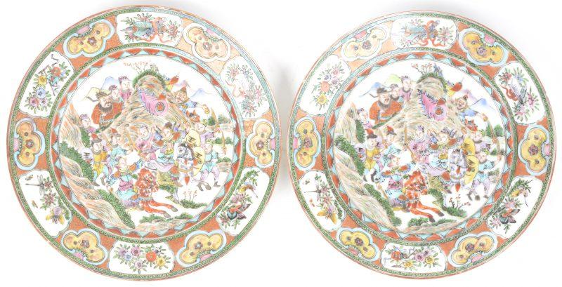 Een paar borden van Chinees porselein met een meerkleurig decor van een veldslag. Onderaan gemerkt.