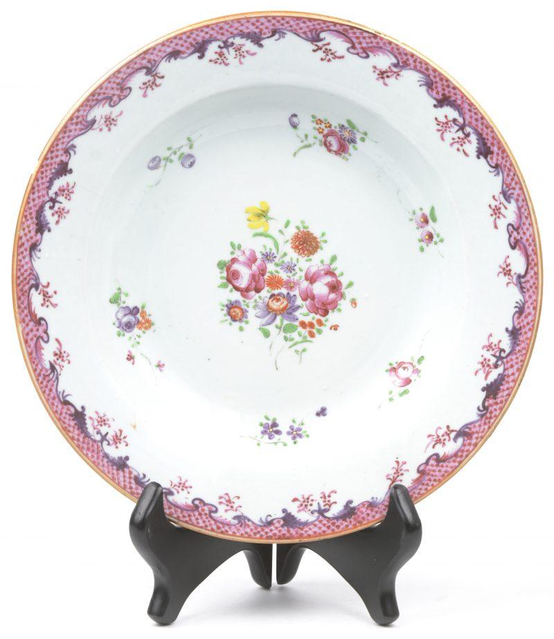 Een diep bord van Chinees porselein met een meerkleurig bloemendecor in de stijl van het Chine de Commande.