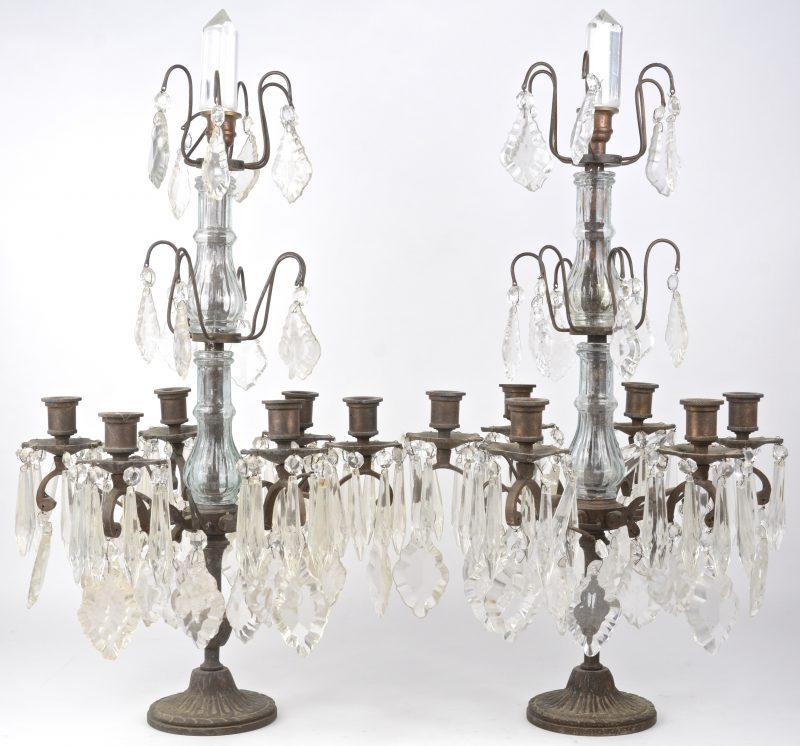 Een paar bronzen girandoles met zes lichtarmen en versierd met kristallen pendeloques.