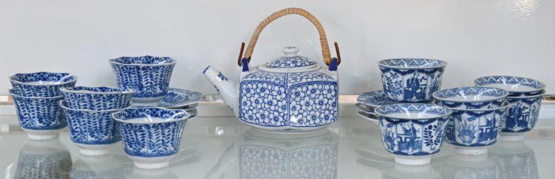 Een Chinees theeservies bestaande uit zes schoteltjes, twee reeksen van zes  kopjes en een theepot. Wit met blauwe florale decoraties.