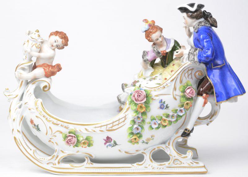 Een groep van meerkleurig en verguld porselein in de vorm van een romantisch koppel en een putto in een gestileerde slee. in de geest van de de XVIIIe eeuw. Onderaan gemerkt.