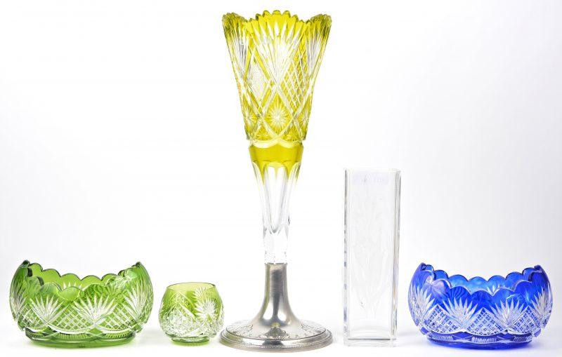 Een lot geslepen Boheems kristal, bestaande uit een kelkvaas op geborsteld metalen voet, een groen en een blauw schaaltje en een klein groen bol vaasje. Bijgevoegd een geslepen kleurloze vierkante vaas.
