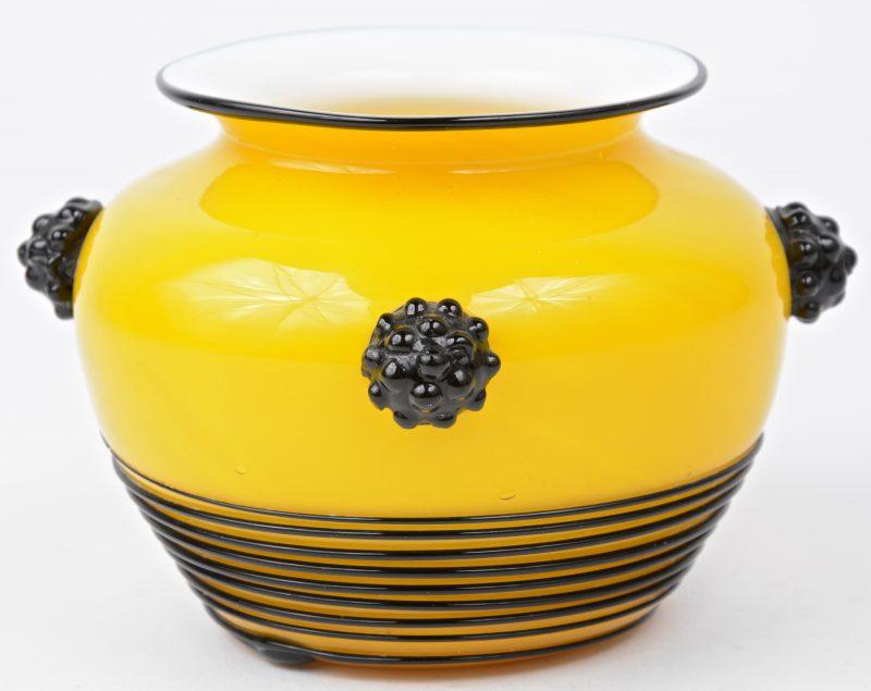 Een geblazen vaasje van geel gas met zwarte versieringen.