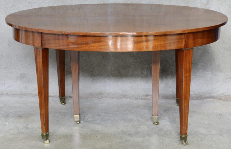 Een verlengbare ovale tafel van mahoniehout met zes tapse poten. Met twee verlengbladen.