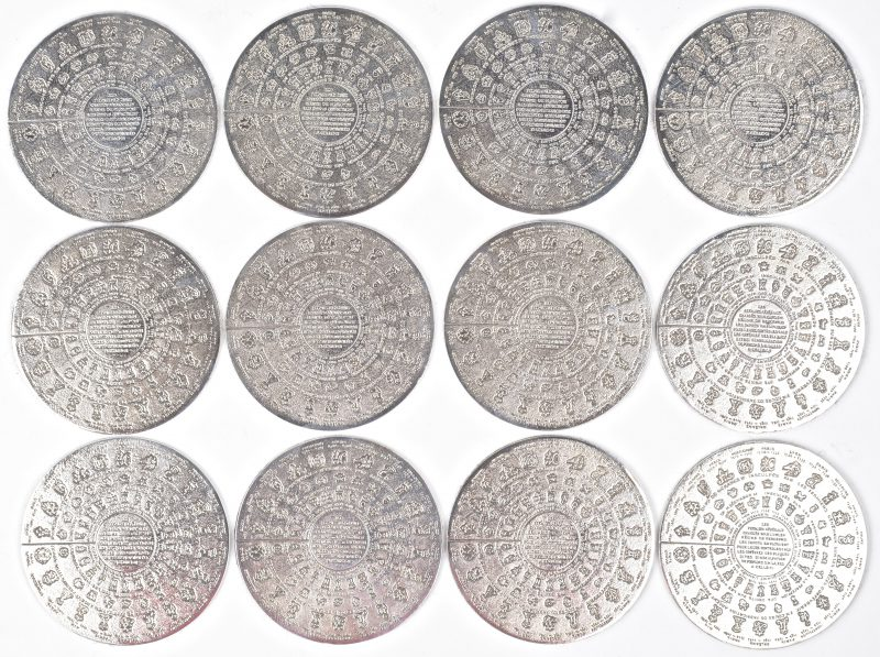 Twaalf verzilverd metalen onderleggers met verschillende zilverkeuren.