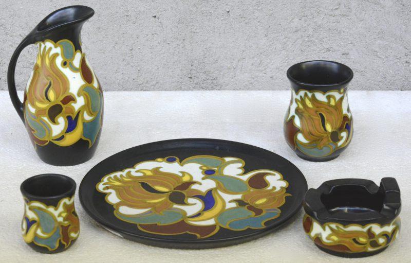 Een asbak, twee bekertjes en een kannetje van meerkleurig Gouda-aardewerk op een bijpassende ronde schotel. Allen gemerkt onderaan.