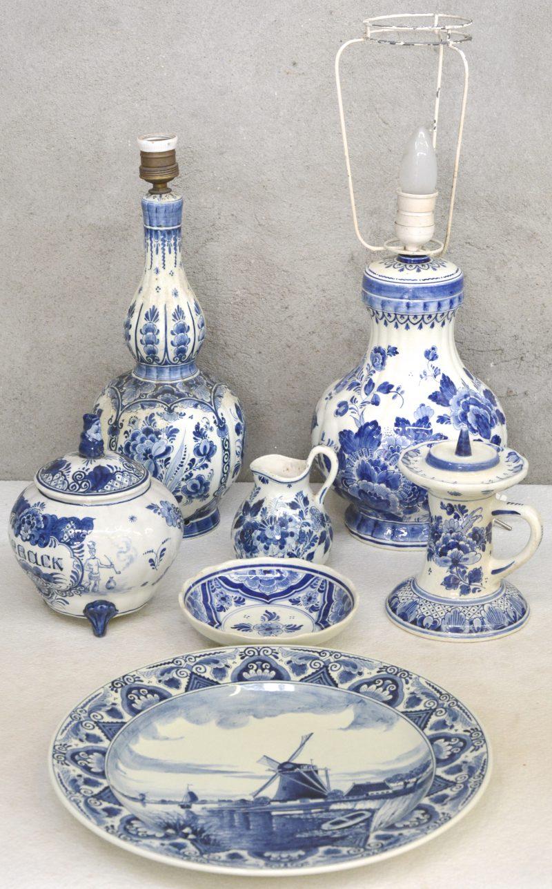 Een lot blauw en wit plateel, bestaande uit twee lampenvoeten, een grote schotel met een Hollands landschap, een kannetje, een kandelaar, een tabakspot en een schaaltje. Allen gemerkt.