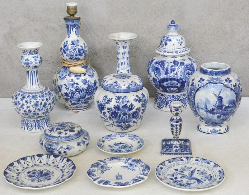 Een lot blauw en wit Delfts plateel, bestaande uit drie dekselvazen (twee zonder deksel), twee verschillende vazen, een lampenvoet, een kleine kandelaar, een dekselpot, drie schaaltjes en een asbak. Allen gemerkt.