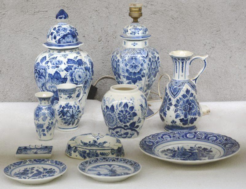 Een lot blauw en wit plateel, bestaande uit een lampvoet, een dekselvaas, een klein vaasje (randschilfers), twee kruiken, een tabakspot zonder deksel, een grote en een kleine asbak, twee kleine en een grote schotel. Allen gemerkt.