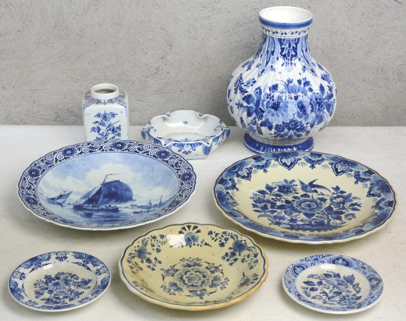 Een lot wit en blauw plateel, bestaande uit een bolle geribde vaas, een vierkante vaas, een asbak, twee sierschotels en drie sierbordjes. Allen gemerkt onderaan.
