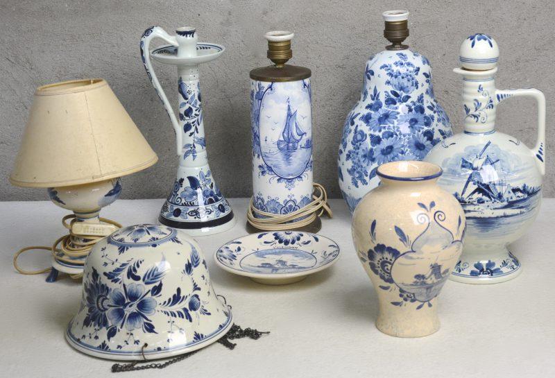 Een lot blauw en wit Hollands plateel, bestaande uit drie verschillende lampen, een hangjardinière, een fles, een hoge kandelaar, een vaas en een sierbord. Diverse merken.