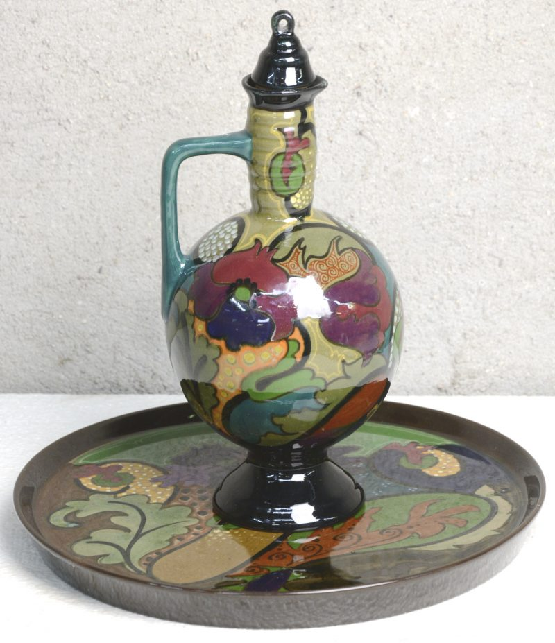 Een kruikje op schotel van meerkleurig Gouds plateel met glanzend glazuur. Onderaan gemerkt.