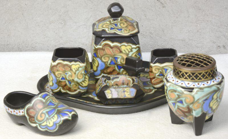 Een lot meerkleurig plateel, bestaande uit een pique-fleur, een klompje, een asbak, een tabakspot en twee kleinere potjes en een plateau.