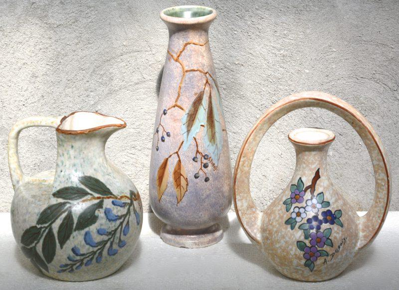 Twee siervazen van meerkleurig aardewerk, versierd met decors van A. Dubois. De langste met enkele kleine schilfers aan de voet. Jaren '10 & '20. Bijgevoegd een vaas van G. Dubois te Baudour.