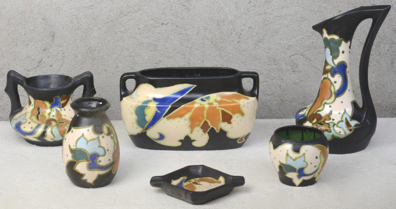 Een lot meerkleurig aardewerk in de stijl van Gouda, bestaande uit een schenkkan, een jardinière, drie vaasjes en een asbak. Onderaan gemerkt.