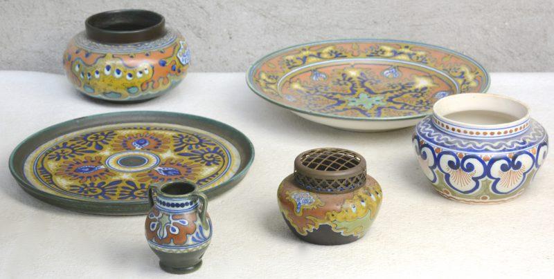 Een lot Gouds plateel met Rhodianglazuur, bestaande uit een diepe schotel, een platte schotel, drie pique-fleurs, waarbij slechts één met montuur en een klein vaasje.