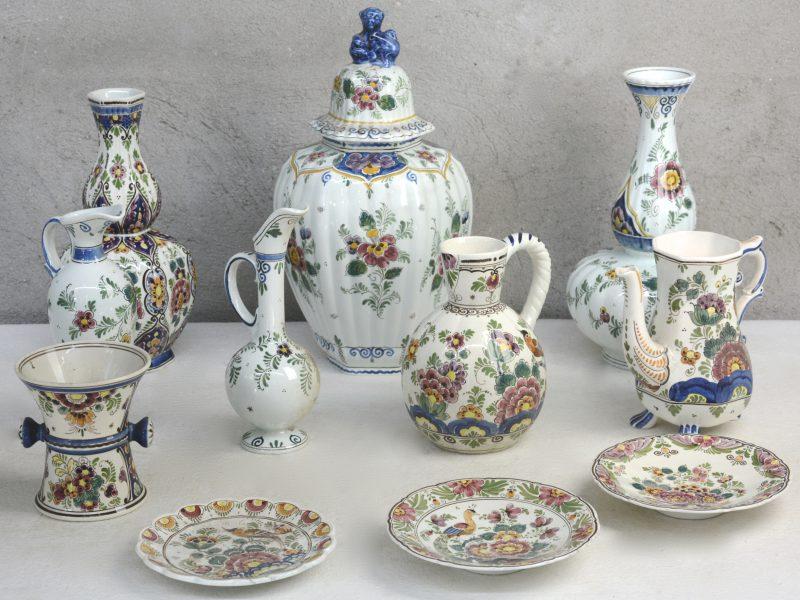 Een lot Hollands plateel meerkleurige Delftse decors, bestaande uit een dekselvaas, twee verschillende knobbelvazen, een schenkkan, twee kruikjes, een vaasje, een theepot zonder deksel en drie schoteltjes.