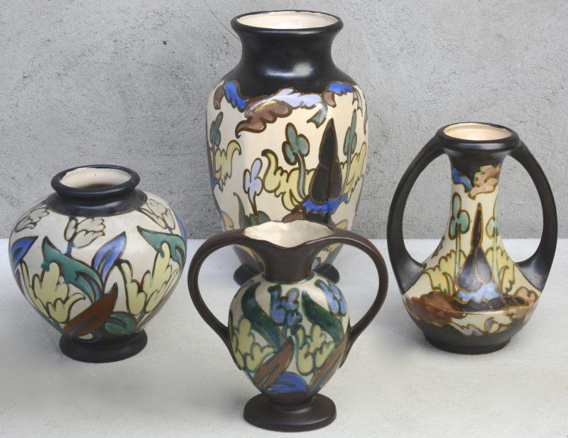 Een lot van vier verschillende vazen van meerkleurig aardewerk in de stijl van Gouda. Onderaan gemerkt.