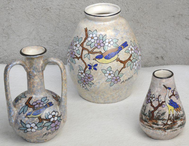 Drie verschillende vaasjes van meerkleurig aardewerk met meerkleurige decors van vogels en bloesems, gesigneerd A. Dubois. Onderaan gemerkt 'Mex'.