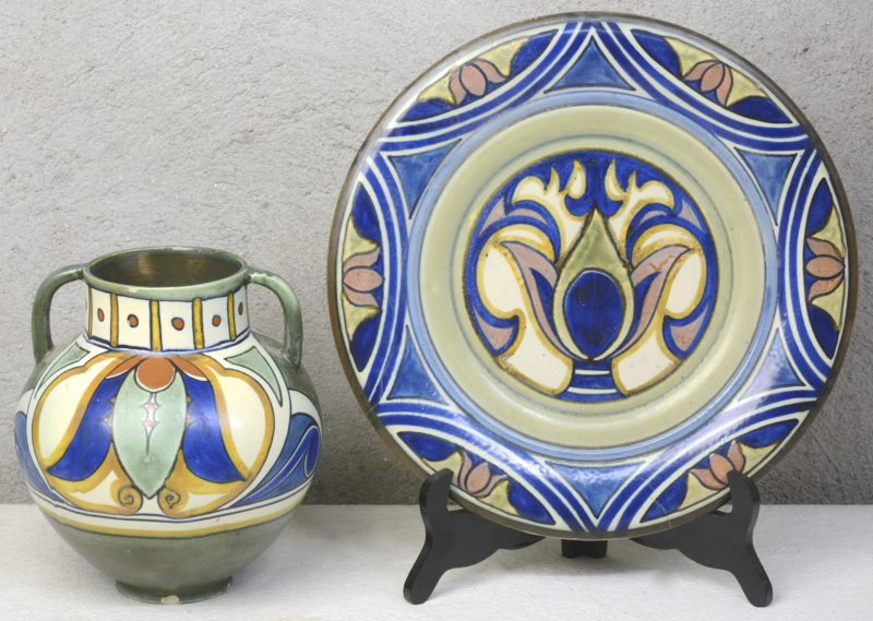Een buikvaas en een schotel van meerkleurig Gouds plateel met Damascusglazuur. Schotel met bakfout, vaas met enkele schilfers. Onderaan gemerkt. Omstreeks 1910.