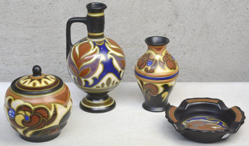 Een lot meerkleurig Gouds plateel, bestaande uit een tabakspot en een vaasje met decor 'Guari' en een kruikje en een asbak met decor 'Ciramat'. Allen gemerkt onderaan.