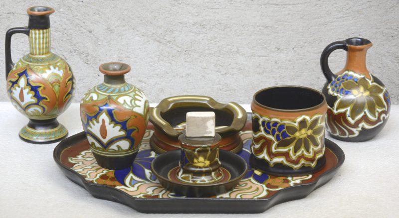 Een lot meerkleurig Gouds plateel, bestaande uit een vaasje en een kruikje met decor 'Ali', een kruikje, een asbak, een luciferhouder en een potje met decor 'Nadro' en een schotel met decor 'Gesina'. Allen gemerkt.