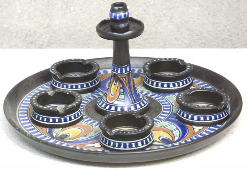 Een ensemble van meerkleurig Gouds plateel, bestaande uit vijf asbakjes en een kandelaar op een ronde schotel. Decor 'Dorcan'. Onderaan gemerkt.