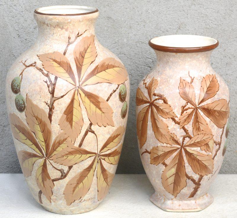 Twee vazen van meerkleurig aardewerk met een decor van kastanjebladeren. Gesigneerd 'A. Dubois'. Onderaan gemerkt.