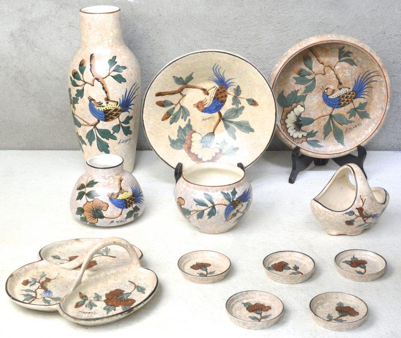Een lot meerkleurig aardewerk met decors van een vogel op een tak, bestaande uit een hoge en twee lage vazen, een mandje, twee schalen, een aperitiefschaal en vijf kleine bordjes. Gesigneerd 'A. Dubois'.