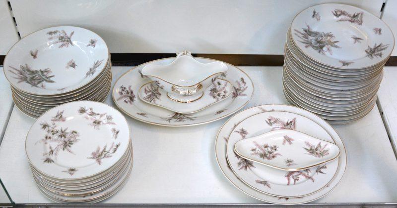 Een servies met een decor van vogeltjes, bestaande uit 29 platte borden en 10 diepe borden, een boterschaaltje, een sauskom, een ronde en een ovale serveerschotel. Gemerkt.