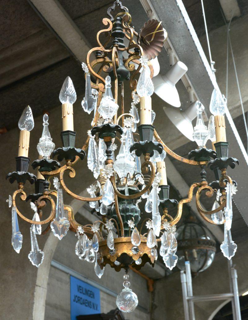 Een bronzen luchter in Regencestijl met zes dubbele lichtpunten en versierd met kristallen pendeloques.