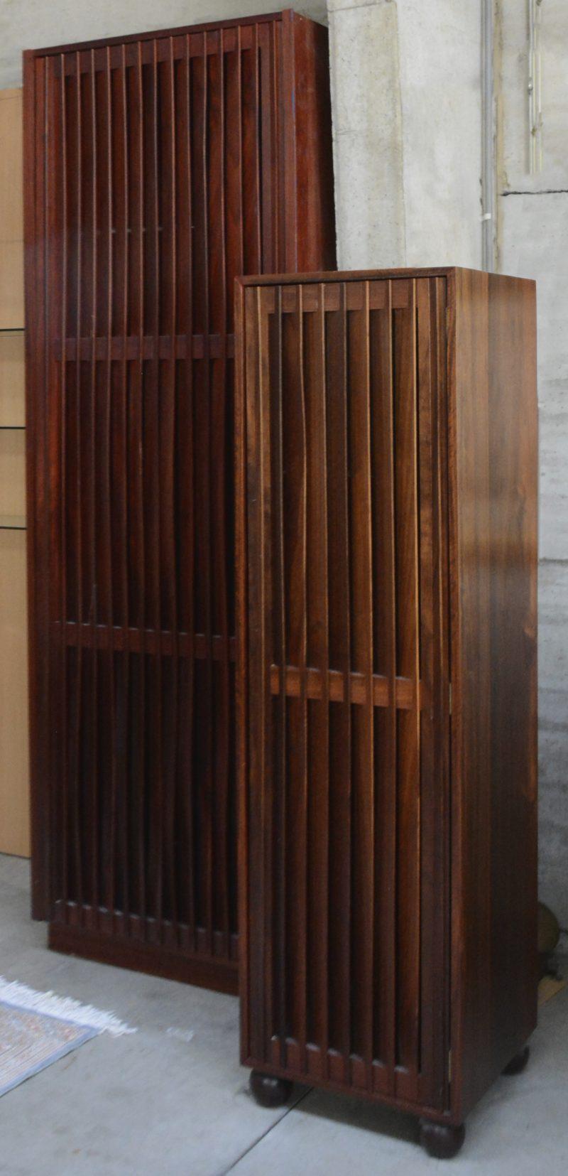 Een lot van twee kleerkasten uit palissanderhout. Periode 1990. Een inbouwkast met twee legplanken en een gechromeerde stang en een vrijstaande kast op bolpoten voorzien van drie legplanken. Lacune aan inbouwkast.